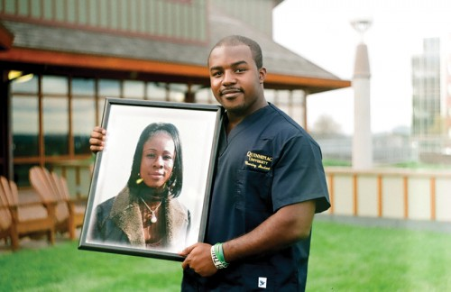 George Buahin poses in his scrubs with a photo of his late mother, Veronica. Buahin says he looks to follow in his mother's footsteps and wants to become a nurse. (Ilya Spektor)