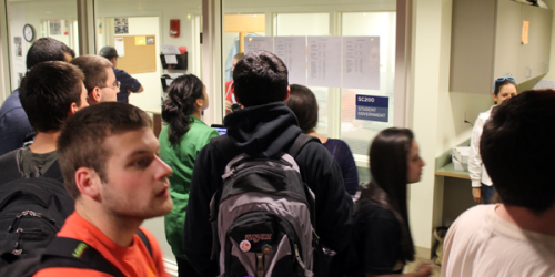 Candidates and students check the election results posted on the window of the SGA suite in the Carl Hansen Student Center Wednesday night.