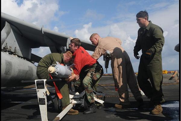 Veteran Matthew Bolton (red sweater) loads a bomb.