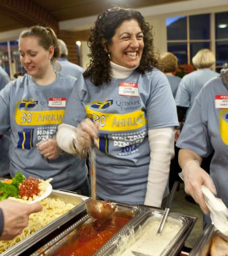 Anna Spragg smiles while serving food at the Undergraduate Holiday Dinner which was held at Quinnipiac University's Carl Hansen Student Center on the Mount Carmel Campus, Thursday, December 4, 2014. Photography by Johnathon Henninger