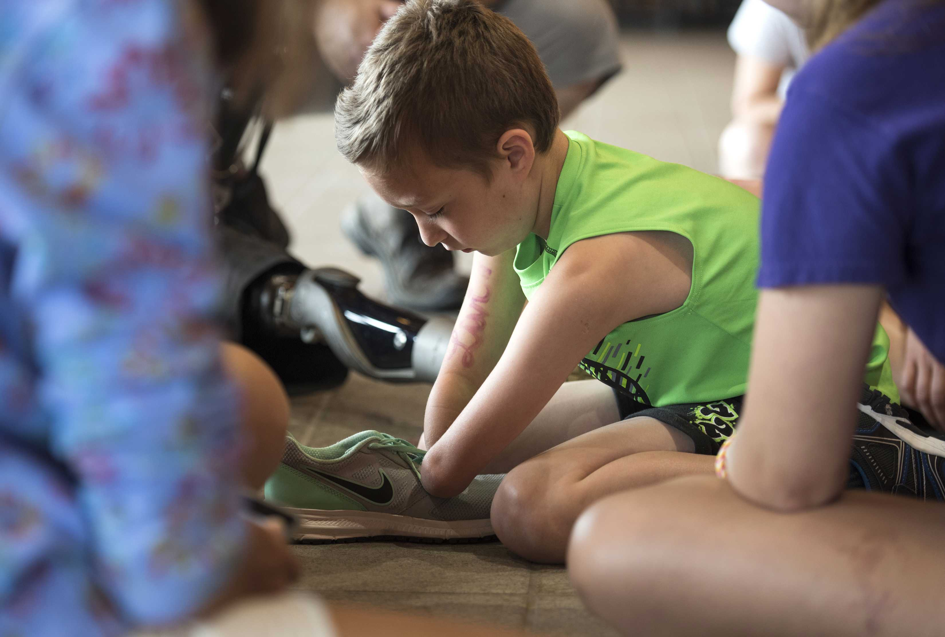 Eight-year-old Sam Becker, of Ithaca, N.Y., learns to tie a knot during an occupational therapy group session on the second day of Camp No Limits Friday,  July 8, 2016, at the Rocky Top Student Center on Quinnipiac University's York Hill Campus.