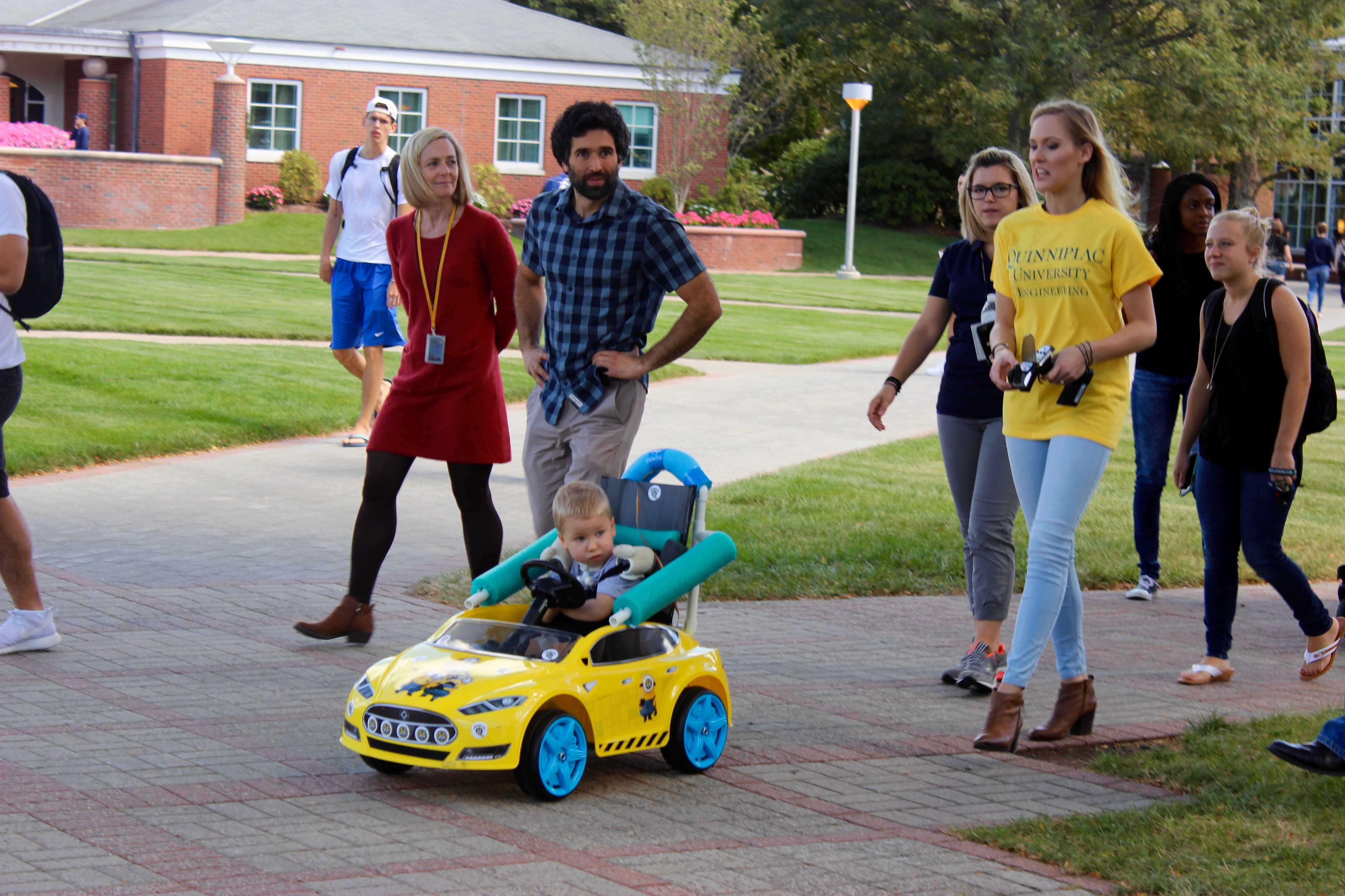 Nolan Green rides around campus in his custom built car, created in part by engineering student Rachel Davis.