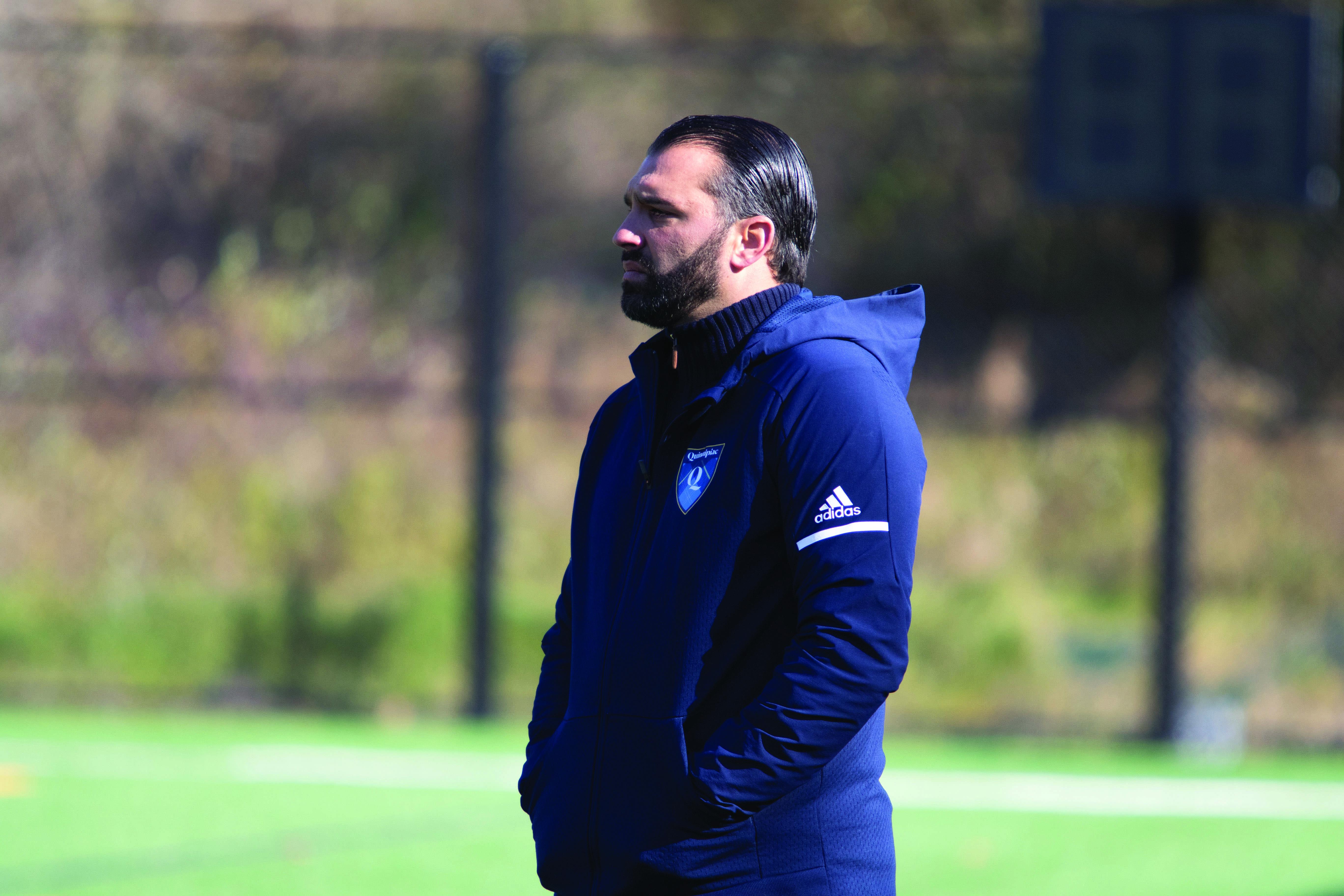 Quinnipiac head coach Eric Da Costa looks on as his team battles on the field.