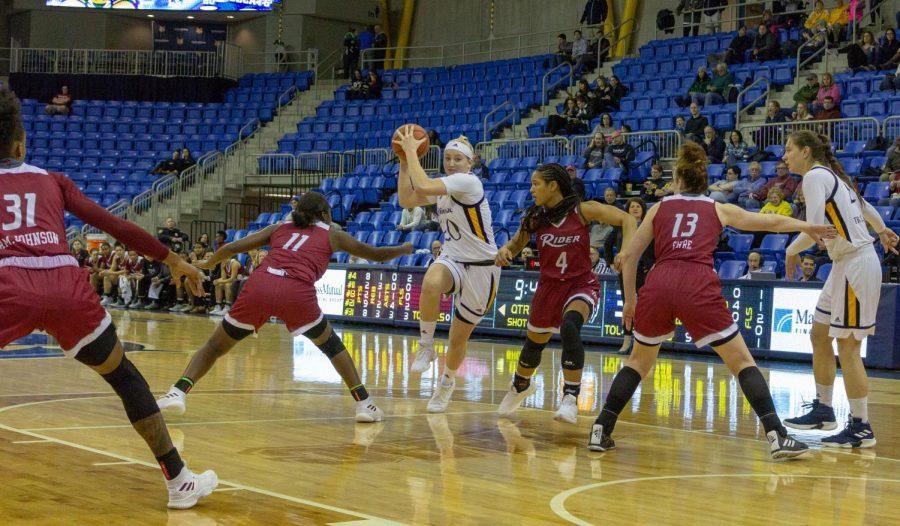 Senior forward Paige Warfel slashes through multiple defenders as she drives toward the rim.