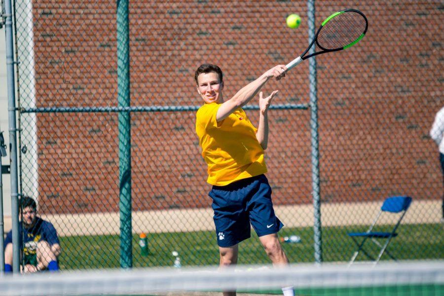 Senior Austin Yannone returns the ball over the net.