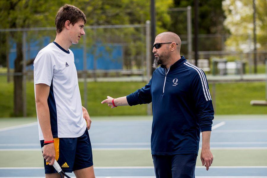 Quinnipiac men's tennis head coach Chris Pappas talks to sophomore Aleksa Martinovic after the match.