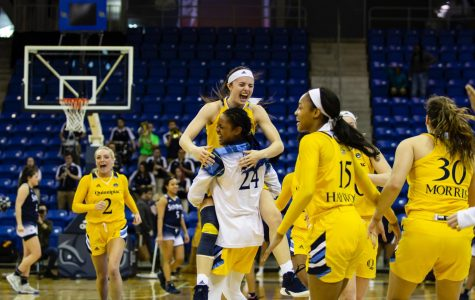 Sophomore guard Mackenzie DeWees leaps into sophomore guard Amani Free's arms following the conclusion of the game.