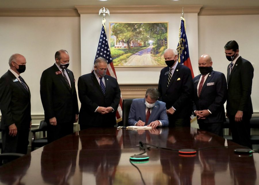 Georgia Gov. Brian Kemp signs a bill targeting minority voters in front of a painting of a plantation that held slaves.