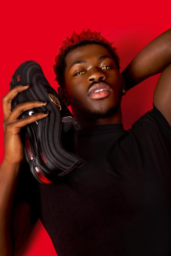 Lil Nas X poses with his 'Satan shoes' custom-made by art collective MSCHF, who Nike has given a restraining order to.