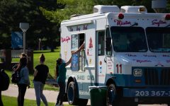 Student is purchasing a cup of chocolate ice cream from Mister Softee truck on campus.