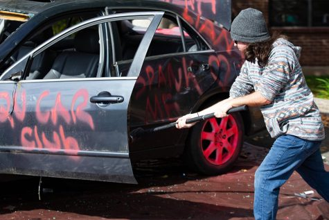 Students relieve their stress at the Car Smash charity event for the Breast Cancer Research Foundation.